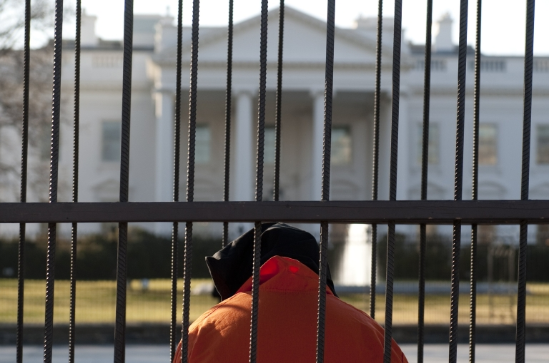 <p>Beth Brockman of the organization Witness Against Torture wears an orange prison jump suit and a hood over her head as she sits in a cage during a demonstration in Lafayette Park outside the White House in Washington, DC, on January 10, 2012, urging the government to close down the detention facility at Guantanamo Bay.</p>