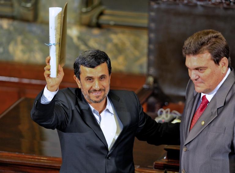 <p>Iranian President Mahmoud Ahmadinejad (L) receives the Doctor Honoris Causa degree from the rector of Havana's University Gustavo Cobreiro, during a ceremony at the university in Havana, on January 11, 2012.</p>