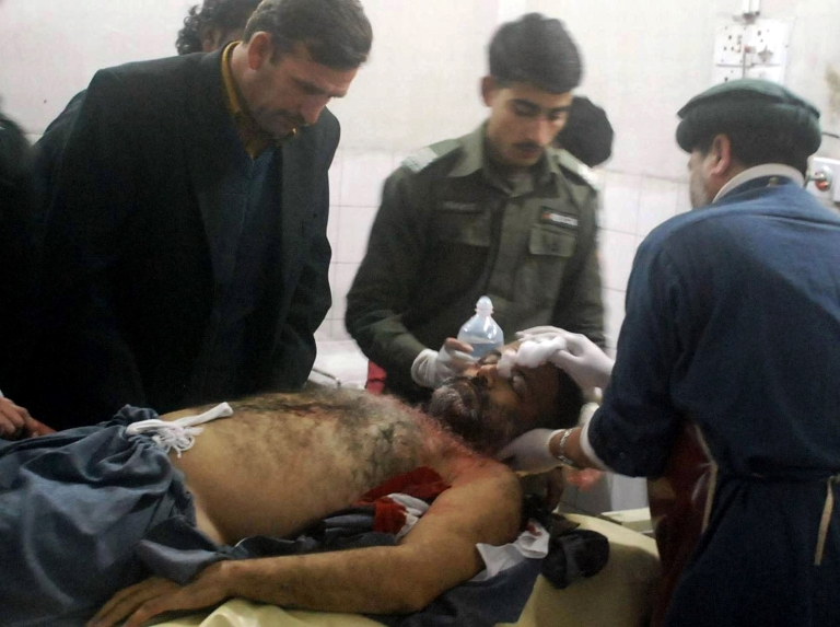 <p>Pakistani paramedics examine the body of a local journalist killed in an attack, at a hospital in Peshawar on January 17, 2012.</p>