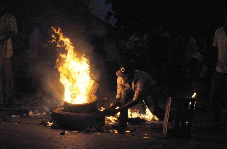 <p>A protester lights a fire on Jan. 31, 2012 in Dakar during a demonstration demanding that President Abdoulaye Wade drop plans to seek a third term. Senegal riot police fired tear gas and sprayed protesters with water to break up the thousands-strong rally.</p>