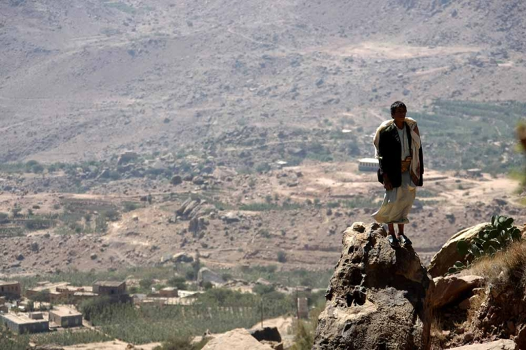 <p>A Yemeni man stands on a rock on February 1, 2012 overlooking a village in Wadi Ahjar, some 50 kms northwest of Sanaa.</p>