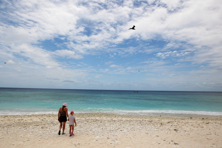 <p>A woman and her daughter walk along the beach at Lady Elliot Island, a resort on the Great Barrier Reef.</p>