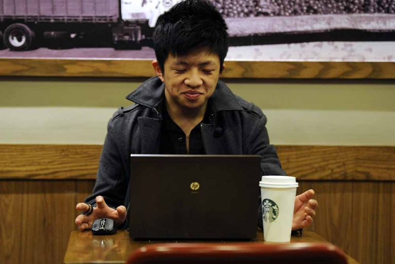 <p>A man uses his computer in a coffee shop in Shanghai on February 2, 2012. PETER PARKS/AFP/Getty Images</p>