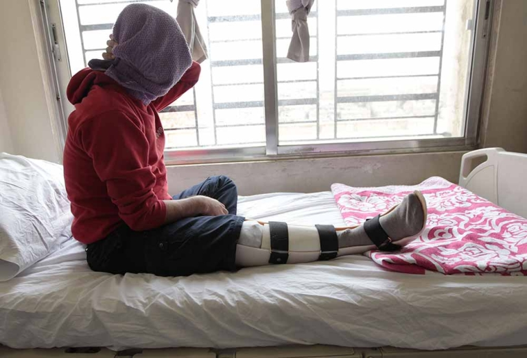 <p>Mohammed, a 27-year-old wounded Syrian brought to Jordan for medical treatment, sits on his hospital bed after undergoing a surgery at the Red Crescent medical institution in Amman on February 12, 2012.</p>