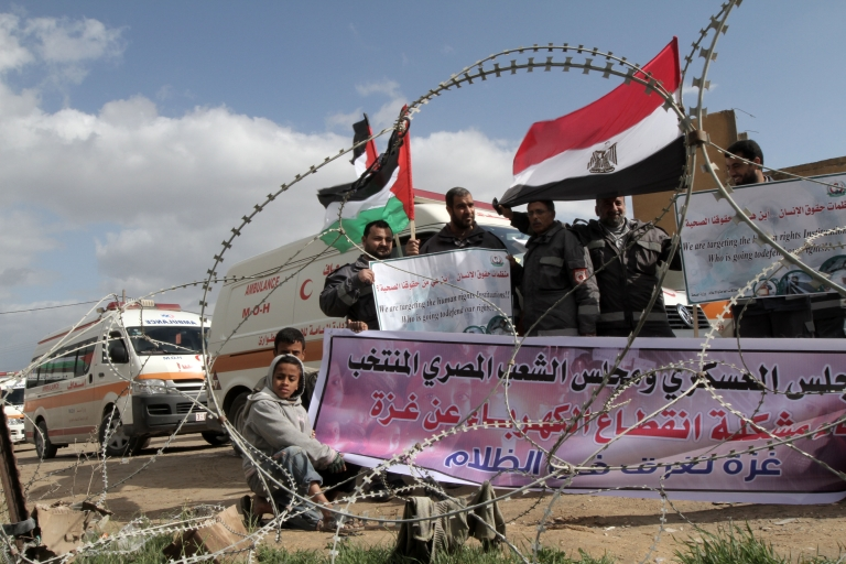 <p>Palestinians attend a rally in front of the Rafah border crossing with Egypt on February 18, 2012 during a sit-in by dozens of emergency crews and ambulance workers demanding Egypt provide the Gaza Strip with electricity and diesel.</p>