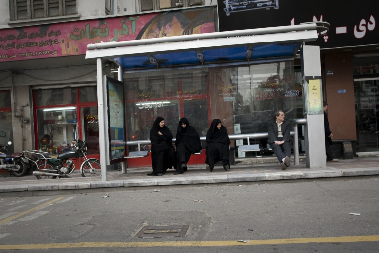 <p>Iranians wait for a public bus at a bus station in central Tehran on February 19, 2012.</p>