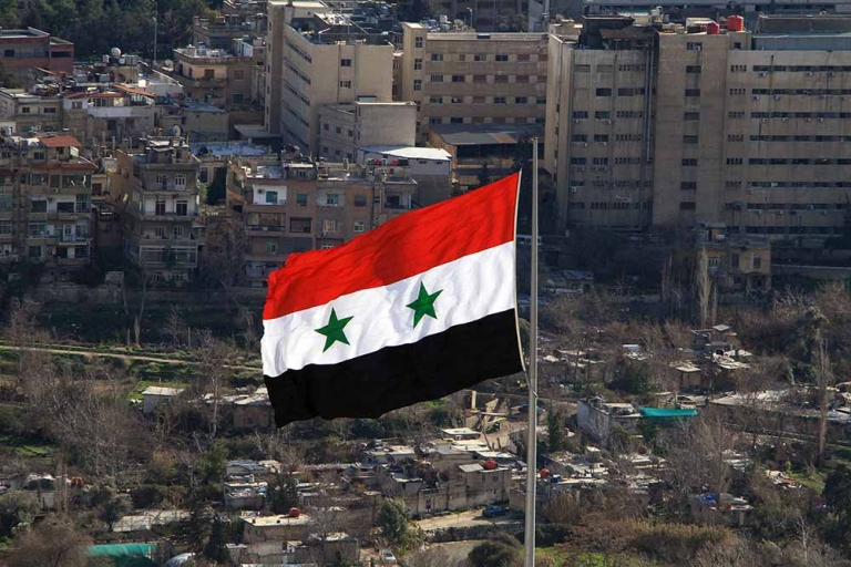 <p>A Syrian flag flies over Damascus on March 1, 2012 .</p>