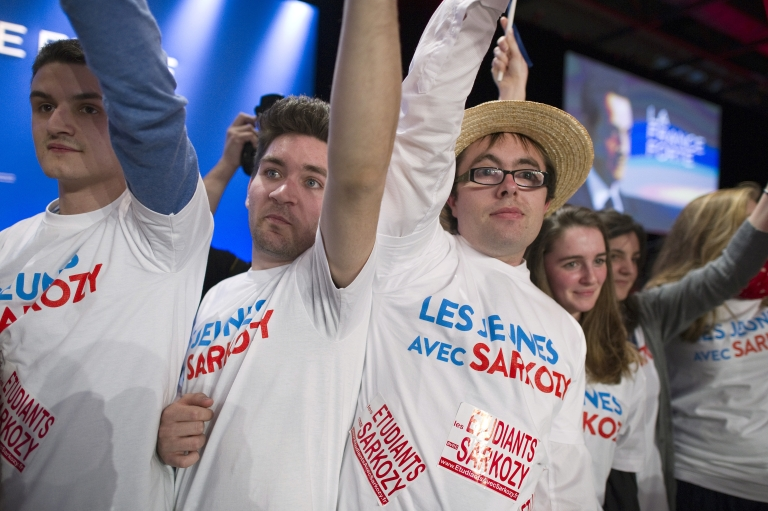 <p>Supporters wearing tee-shirts reads 'Young people with Sarkozy' waves flags as they listen France's ruling party UMP candidate for the 2012 French presidential election Nicolas Sarkozy during a campaign meeting, on March 3, 2012 in the southwestern city of Bordeaux.</p>