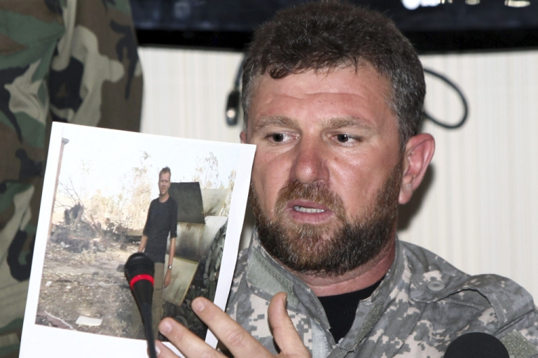 <p>The commander of the Libyan Swehli militia, Faraj Swehli, holds up a photograph of British journalist Gareth Montgomery-Johnson during a press conference in Tripoli.</p>