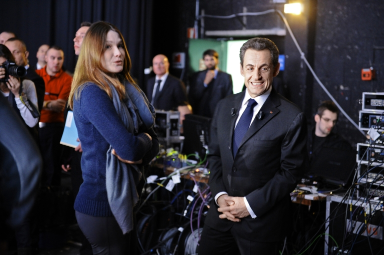 <p>France's incumbent president and UMP ruling party candidate for the 2012 presidential election Nicolas Sarkozy (R) waits beside France's First Lady Carla Bruni-Sarkozy before taking part in the TV broadcast show 'Des paroles et des actes' of French TV channel France 2 on March 6, 2012 in Paris.</p>