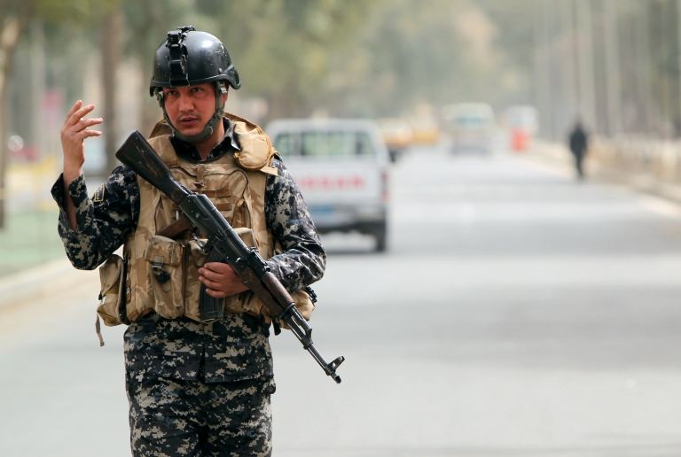 <p>An Iraqi security officer mans a checkpoint in Baghdad.</p>