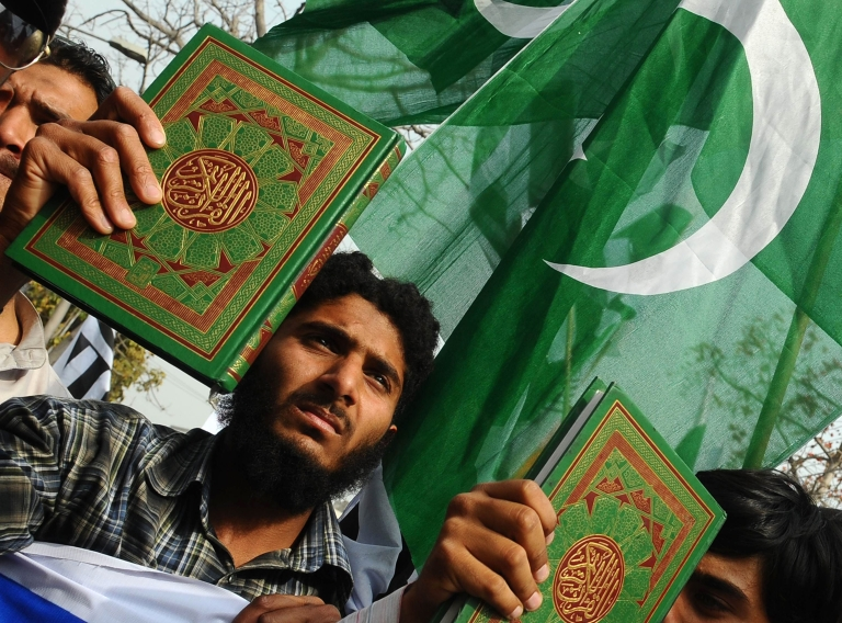 <p>Deaf Pakistani men carry the Koran and placards during a protest in Lahore on March 18, 2012, over the burning of Korans in Afghanistan.</p>