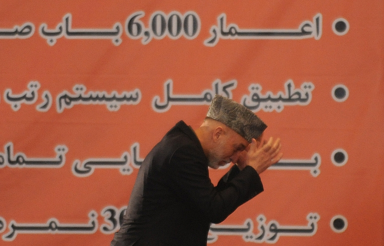 <p>Afghan President Hamid Karzai walks onstage to deliver his address during a ceremony marking the start of the new school year at Amani High School in Kabul on March 24, 2012.</p>
