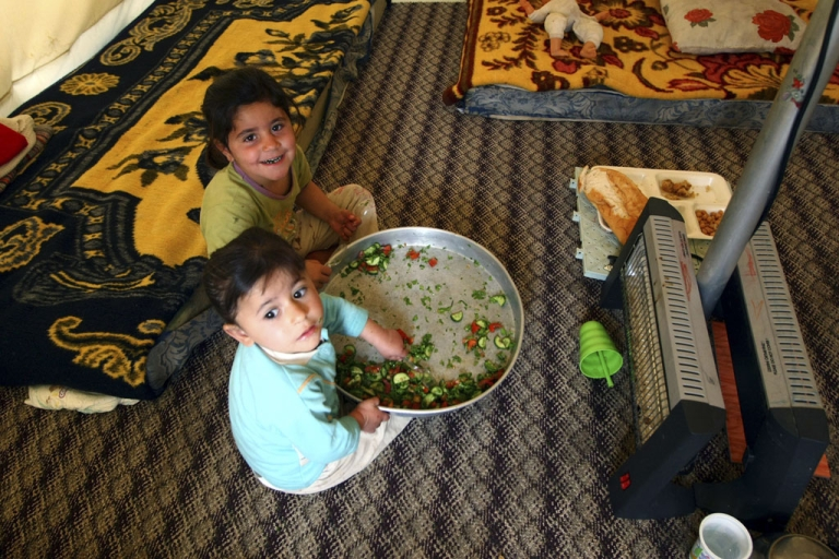 <p>Syrian refugee children eat in a tent at the Red Crescent camp in Boynuyogun, Turkey, near the Syrian border. The Boynuyogun camp holds some 2,000 Syrian refugees in 600 tents.</p>