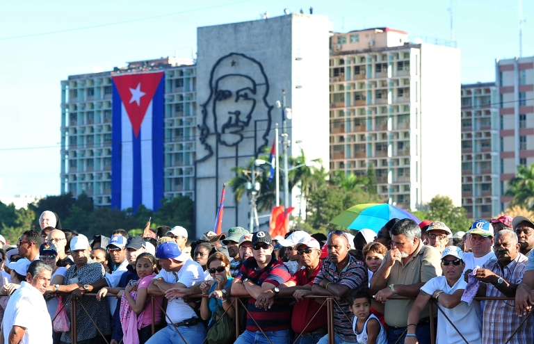 <p>Believers wait for the Pope Benedict XVI nearby a huge portrait of Cuban revolutionary Che Guevara at Revolution Square in Havana, on March 28, 2012.</p>