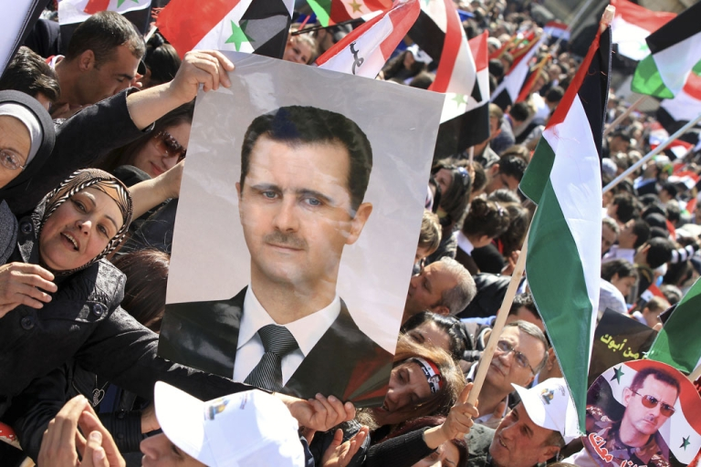 <p>A Syrian woman holds a picture of President Bashar al-Assad as other protestors fly Palestinian and pre-Baath Syrian flags during a demonstration to mark Land Day in Damascus today. Canada and the US imposed further sanctions against Assad, his family and military leaders today.</p>
