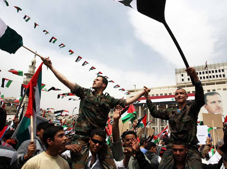 <p>Syrian soldiers from the government wave Syrian flags during a march in Damacus on April 7, 2012 to celebrate the anniversary of the founding of the Baath Party and in support of President Bahsar al-Assad (portrait). Tens of thousands of Syrian protesters also took to the streets for anti-government rallies, activists said, as regime forces pounded rebel cities, earning a stern rebuke from UN chief Ban Ki-moon.</p>