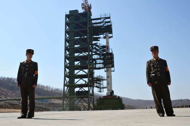 <p>Two North Korean soldiers stand guard in front of the Unha-3 rocket at Tangachai -ri space center on April 8, 2012.</p>
