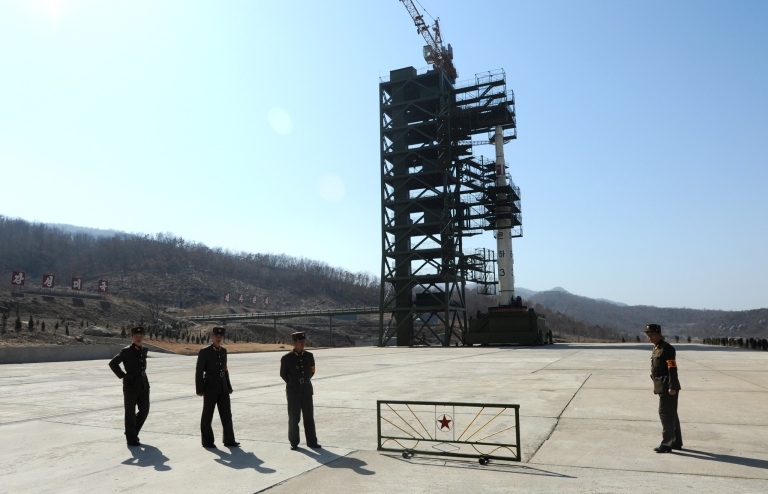 <p>North Korean soldiers stand guard in front of the Unha-3 rocket at Tangachai -ri space center on April 8, 2012.</p>