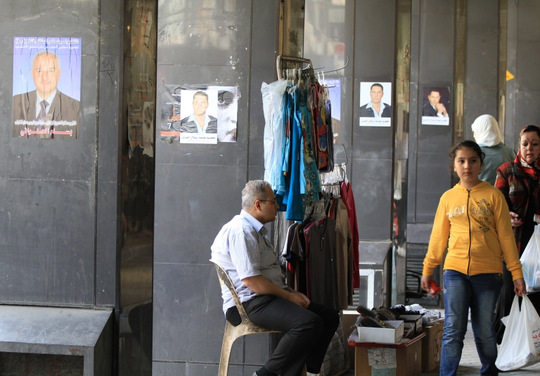 <p>Syrian shoppers walk in front of posters for parliamentary candidates in Damascus on April 12, 2012, as a UN-backed ceasefire went into effect.</p>