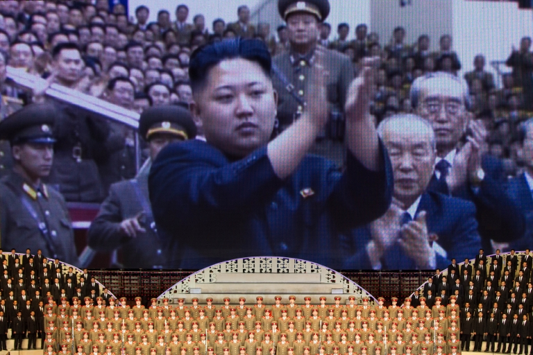 <p>North Korean performers sit beneath a screen showing images of leader Kim Jong-Un at a theatre during celebrations to mark the 100th birth anniversary of the country's founding leader Kim Il-Sung, in Pyongyang on April 16, 2012.</p>