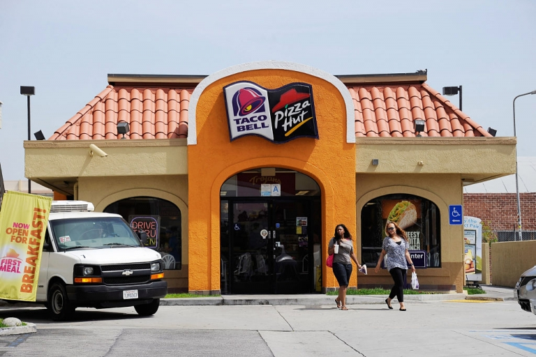 <p>LOS ANGELES, CA - APRIL 19:  Customers walk to a Taco Bell and Pizza Hut restaurant during lunchtime on April 19, 2012 in Los Angeles, California. Yum Brands Inc., the parent company of KFC, Taco Bell and Pizza Hut chains, reported dramatically strong first quarter earnings.</p>
