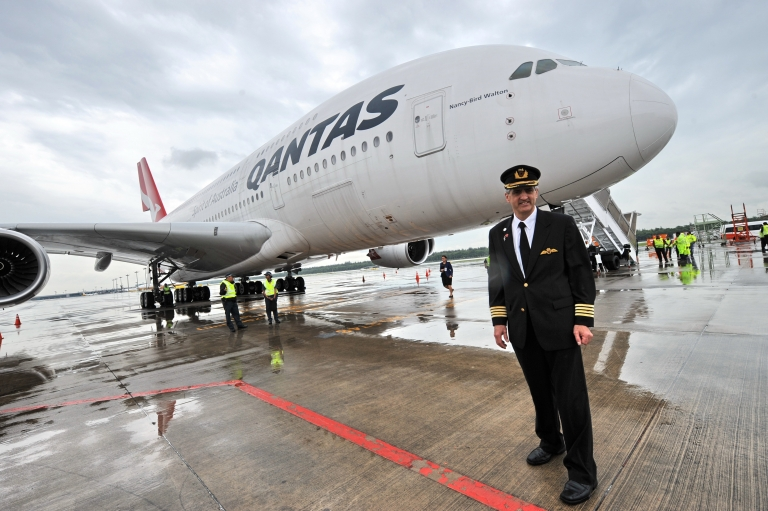 <p>Qantas pilot captain Richard de Crespigny poses infront of the Qantas Airbus A380 jet dubbed 'Nancy Bird Walton', in honour of Australia's first female commercial pilot, on the tarmac at the Changi International Airport in Singapore on April 21, 2012. A Qantas Airbus A380 jet that dramatically lost an engine in a mid-air blast off Singapore in November 2010 was formally handed back to the Australian flag carrier April 21 after extensive repairs.</p>