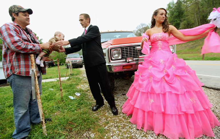 <p>Dates Coty Shouse (C) and Destiny Duff (R) gather as Destiny's father Ronnie Duff (L) passes a baby to be photographed while preparing for the Owsley County High School prom on April 21, 2012 in Booneville, Kentucky.</p>