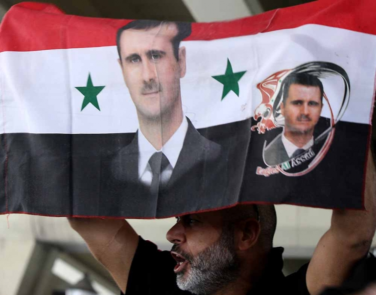 <p>A Syrian man holds his national flag bearing pictures of Syrian President Bashar al-Assad during a pro-regime protest to condemn a deadly blast in the central Midan district of Damascus on April 27, 2012.</p>