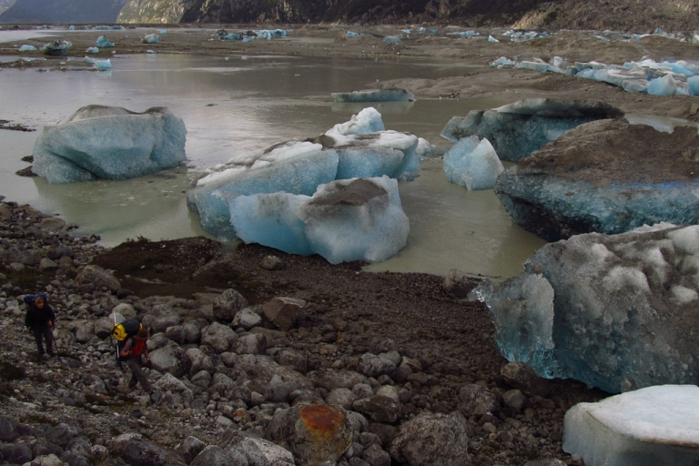 <p>Two people walk next to ice blocks in the lake Cachet II in Aysen, Chilean Patagonia, 1700 Kms south of Santiago on April 6, 2012. Shortly before midnight of March 31, 2012 the lake with his 200 million liters of water began empty for second time this year. The lake disappeared completely due to rising temperatures driven by climate change, according to experts.</p>