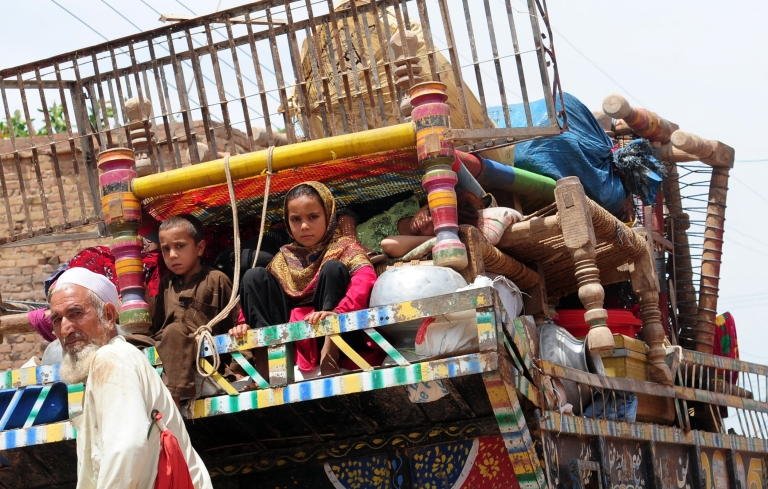 <p>A Pakistani tribal family sit in a mini truck with their belongings as they evacuate from Shlober conflict area, in Bara town of Khyber tribal district on May 7, 2012 following a military campaign launched against the militants.</p>