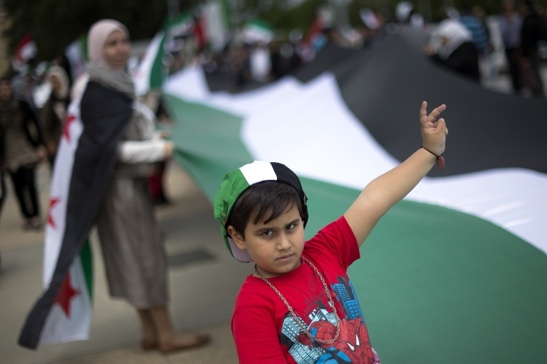 <p>A child flashes a victory sign as he takes part in a European demonstration against the Syrian regime, calling for democracy and an end to bloodshed in Syria, on May 19, 2012, in Geneva.</p>