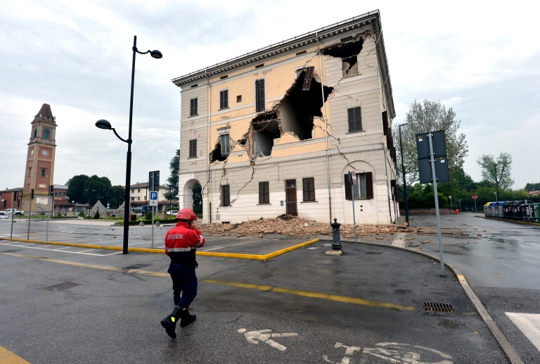 <p>A rescue walks in front of the facade of the town hall after a powerful earthquake that shook Italy's industrial and densely populated northeast early on May 20, 2012 in Sant'Agostino village in the Modena province killing at least six people, felling homes and factories and toppling church steeples.</p>