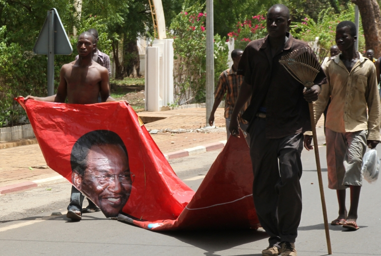 <p>Two Malians drag a portrait of Mali's transition president Diancounda Traore as they take part in a protest with thousands of pro-junta supporters on May 21, 2012 in Bamako.</p>
