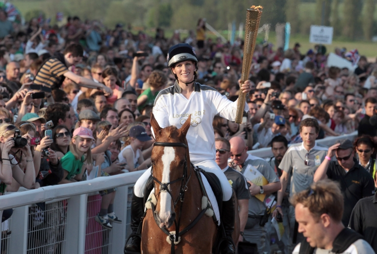 <p>Olympic torchbearer Zara Phillips arrives on her horse Toy Town as she brings Olympic flame to Cheltenham Racecourse on May 23, 2012</p>
