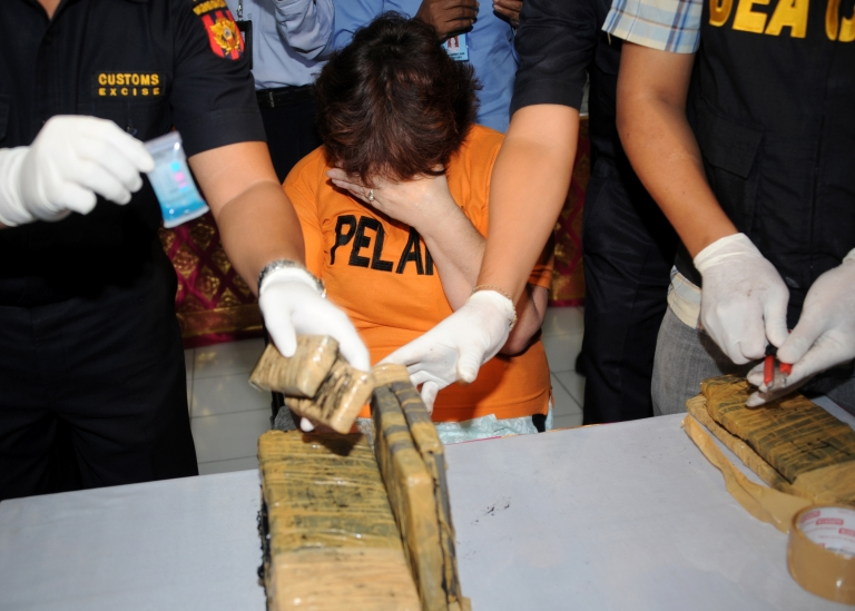 <p>Linsay June Sandiford (C), 56, of Britain covers her face as customs personnel display evidence at a customs office in Denpasar on Bali island on May 28, 2012. Sandiford was arrested on May 19 carrying 4.7 kilogramms of cocaine in her luggage at Bali International Airport in Indonesia, official said.</p>