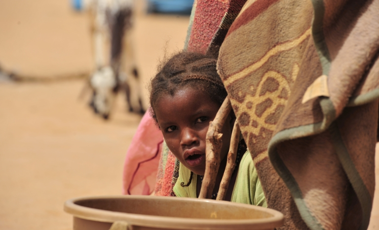 <p>A young refugee from northern Mali looks out from her tent inside the UNHCR Mangaize refugee camp, 100 miles north of Niamey, on June 2, 2012.</p>