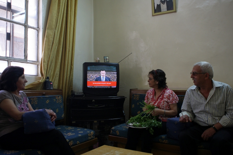 <p>Syrians listen to the televised speech of Syrian President Bashar al-Assad at their house in Damascus on June 3, 2012.</p>
