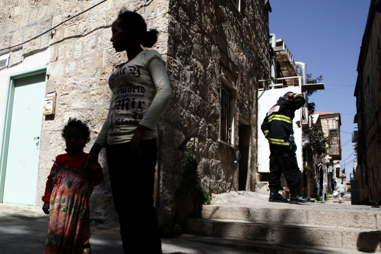<p>An Eritrean woman stands with her daughter outside an apartment which is home to African migrants after unknown attackers set it ablaze overnight in Jerusalem on July 4, 2012.</p>