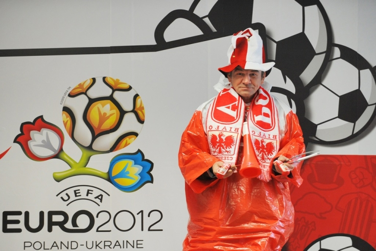 <p>A Polish fan outfits seller stands next to a UEFA Euro 2012 tournament banner downtown Wroclaw on June 5, 2012 ahead of the Euro 2012 football championships which will start on June 8 in Warsaw.</p>