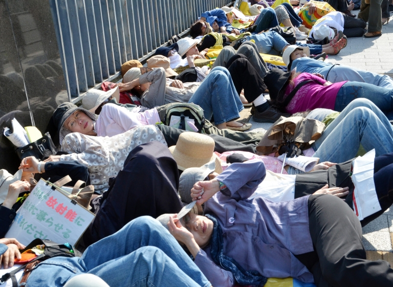 <p>About 100 female activists, mainly from Fukushima prefecture, stage a die-in protest in front of the prime minister's official residence in Tokyo on June 7, 2012.</p>