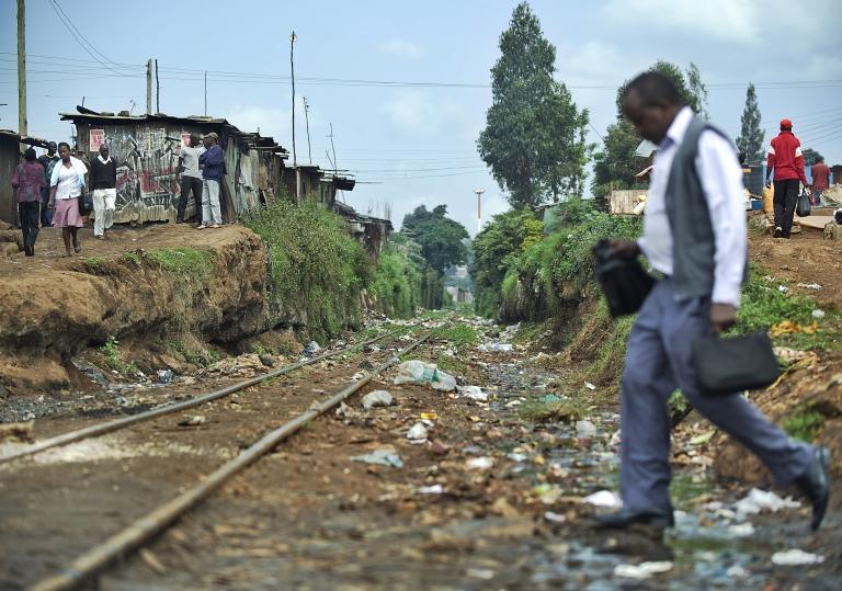 <p>A man walks over an open sewer on June 8, 2012 at Kibera slum, in the Kenyan capital Nairobi.</p>