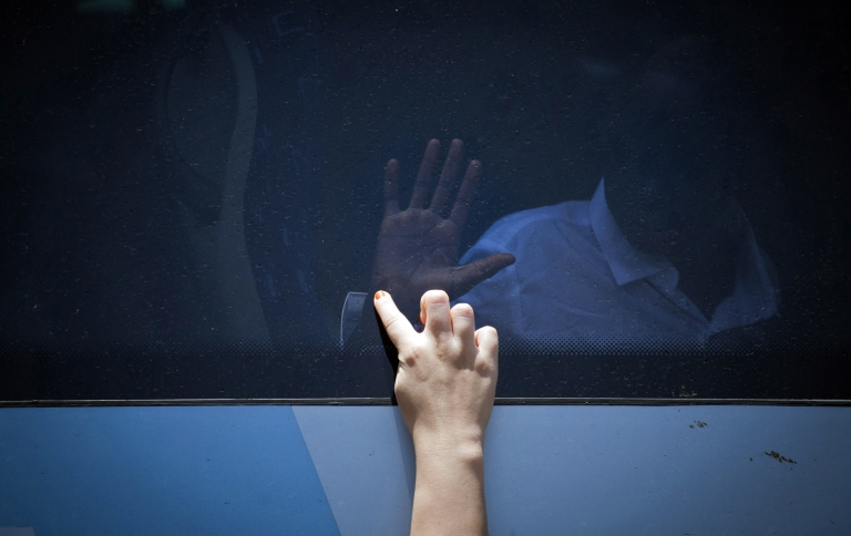 <p>Two girls divided by the bus window, touch hands as South Sudanese refugees board a bus taking them to Ben Gurion International airport, near Tel Aviv.</p>