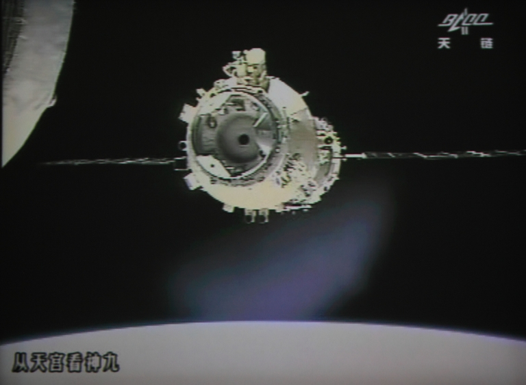 <p>A photo of the giant screen at the Jiuquan space center shows the Shenzhou-9 spacecraft approching Tiangong-1 module for the automatic docking on July 18, 2012.</p>