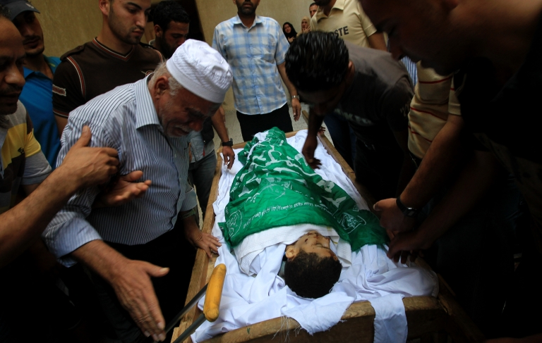 <p>Relatives of 14-year old Moamen al-Adam, who was killed in an Israeli air strike the day before, mourn during his funeral in Gaza city on June 21, 2012. The latest attacks follow three days of violence in which eight Palestinians were killed in Israeli air strikes while militants fired scores of rockets at the Jewish state, one of which slammed into a border police outpost, wounding four.</p>