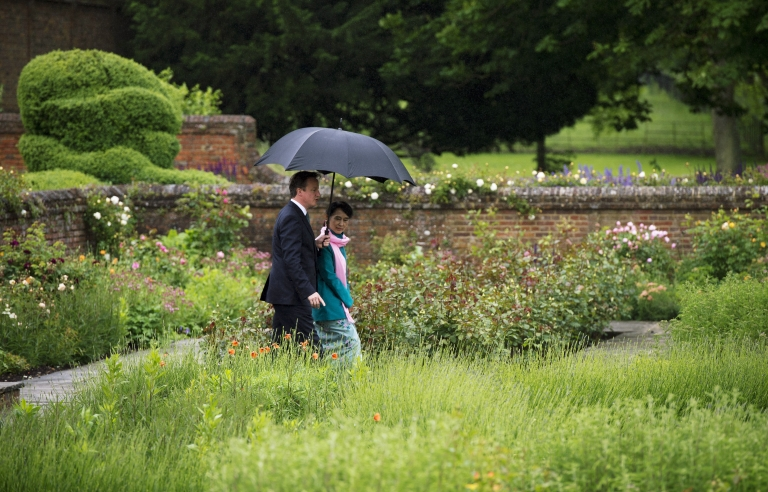 <p>Britain's Prime Minister David Cameron (L) speaks with Myanmar democracy icon Aung San Suu Kyi as they walk in the rose garden at Chequers, the Prime Minister's official country residence, in Buckinghamshire, west of London, on June 22, 2012.</p>