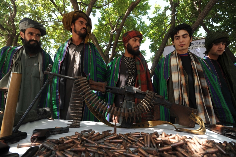 <p>Former Taliban fighters display their weapons as they join Afghan government forces during a ceremony in Herat province on June 23, 2012. Ten fighters left the Taliban to join government forces in western Afghanistan.</p>