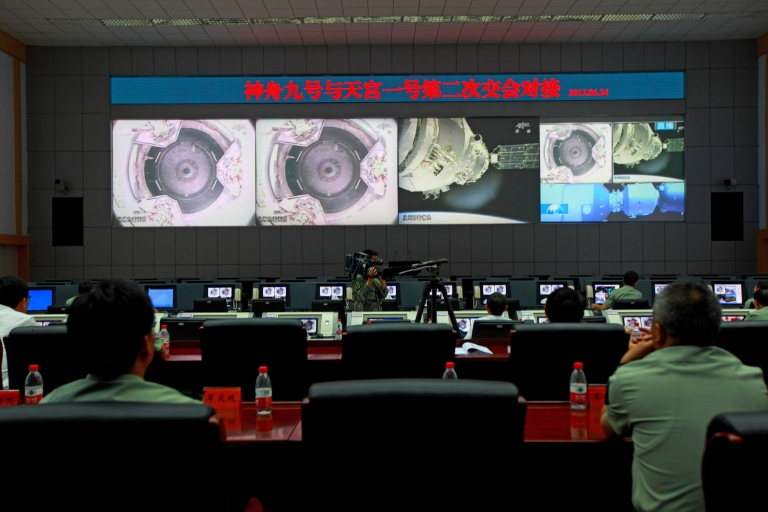 <p>Chinese technicians at the Jiuquan Space Centre monitor the Shenzhou-9 spacecraft as it prepares to link with the Tiangong-1 module just over a week into a manned space mission which includes China's first female astronaut, following an automatic docking, on June 24, 2012.</p>