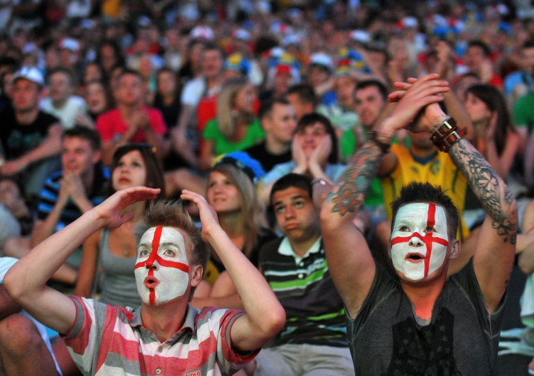 <p>England's fans react as they watch the quarter- final match England vs Italy on giant screen in Kiev on June 24, 2012. One Chinese fan died while watching every single match in the Euro 2012.</p>