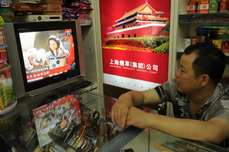 <p>A shop owner watches television in his store in Shanghai as China's first female astronaut Liu Yang is shown getting out of the return capsule of the Shenzhou-9 spacecraft after returning to earth on June 29, 2012.</p>